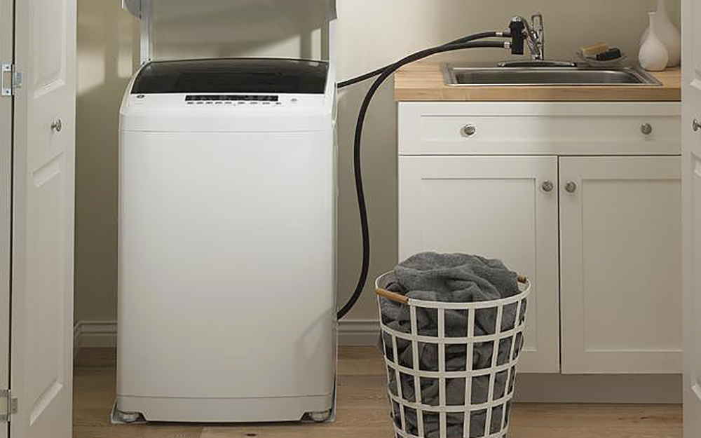 A portable washer with a water line hooked up to a sink in a small laundry space.