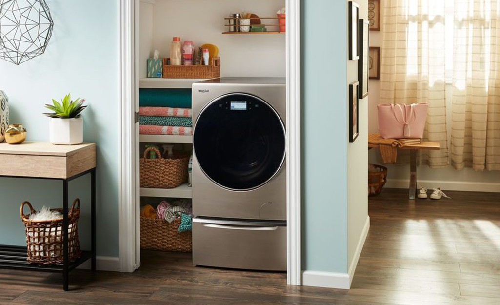 A washer/dryer combo in a small laundry room.
