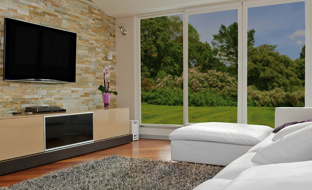 Temperature control window film covering floor-to-ceiling windows in a home.