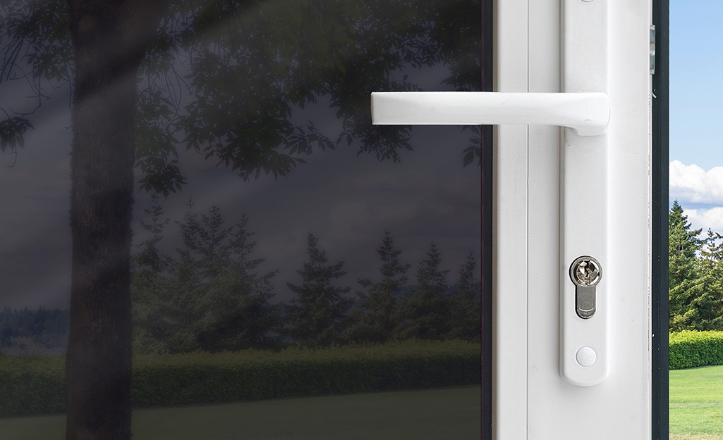 Close-up of a glass exterior door covered with dark security film
