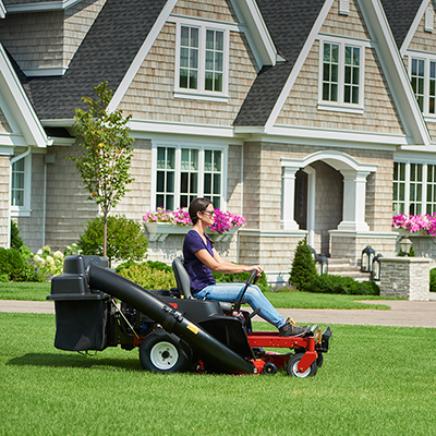 Woman in jeans mowing lawn with a zero turn mower.