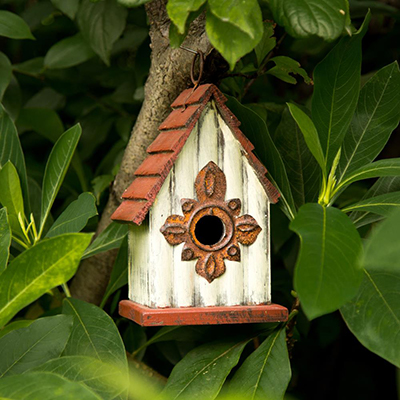 A white birdhouse with a red roof hanging in a tree.