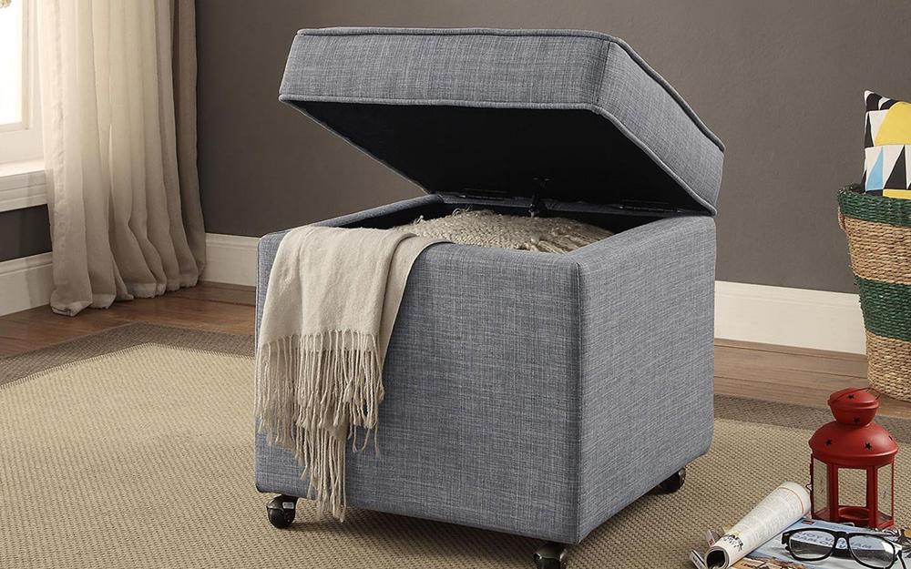Một chiếc ghế đẩu có nắp mở, bên trong có một tấm chăn.
