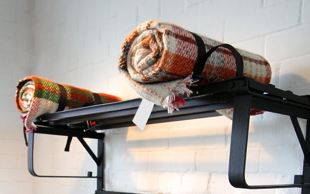 Chăn được cuộn lại và cất trên giá treo khăn.