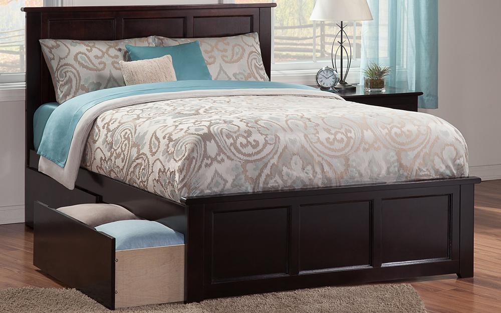 Một chiếc giường với ngăn kéo mở bên dưới, bày những chiếc chăn được cất giữ.