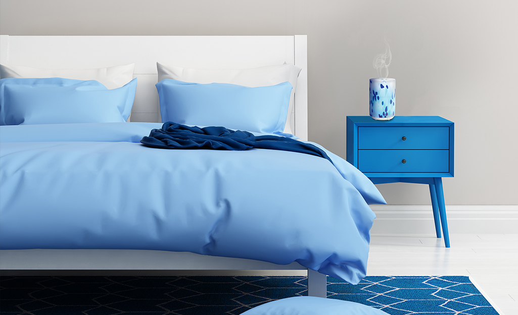 A bedroom with furniture, bedding and decor in different shades of blue.