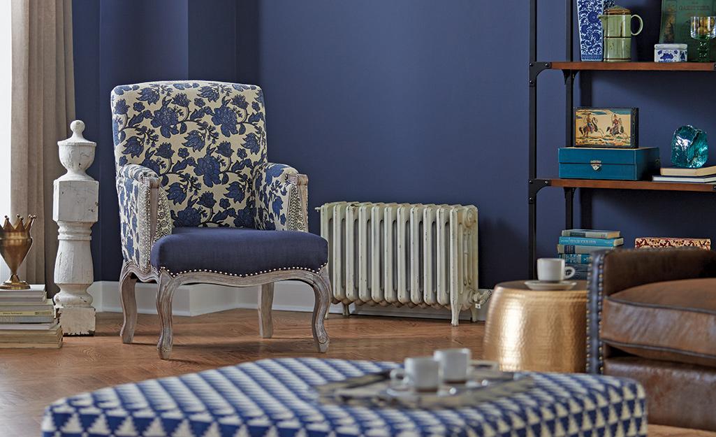 Một chiếc ghế hoa rất hợp với một chiếc ghế dài có hoa văn chevron trong phòng khách màu xanh lam.