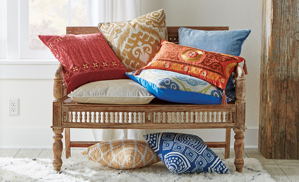 Trang trí theo phong cách Boho sử dụng gối ném với nhiều màu sắc, kiểu dáng và kết cấu khác nhau trên băng ghế gỗ.