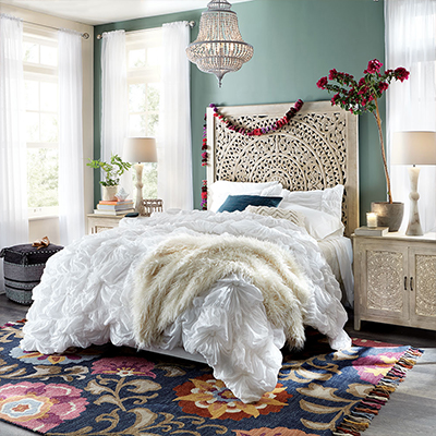 A bedroom with boho decor, including textured, layered bedding, a beaded chandelier, a carved headboard and a colorful accent rug.