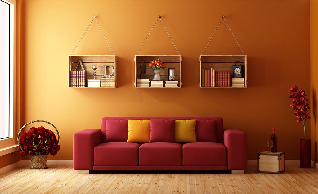 Ba chiếc thùng gỗ được dùng làm giá sách treo tường phòng khách.