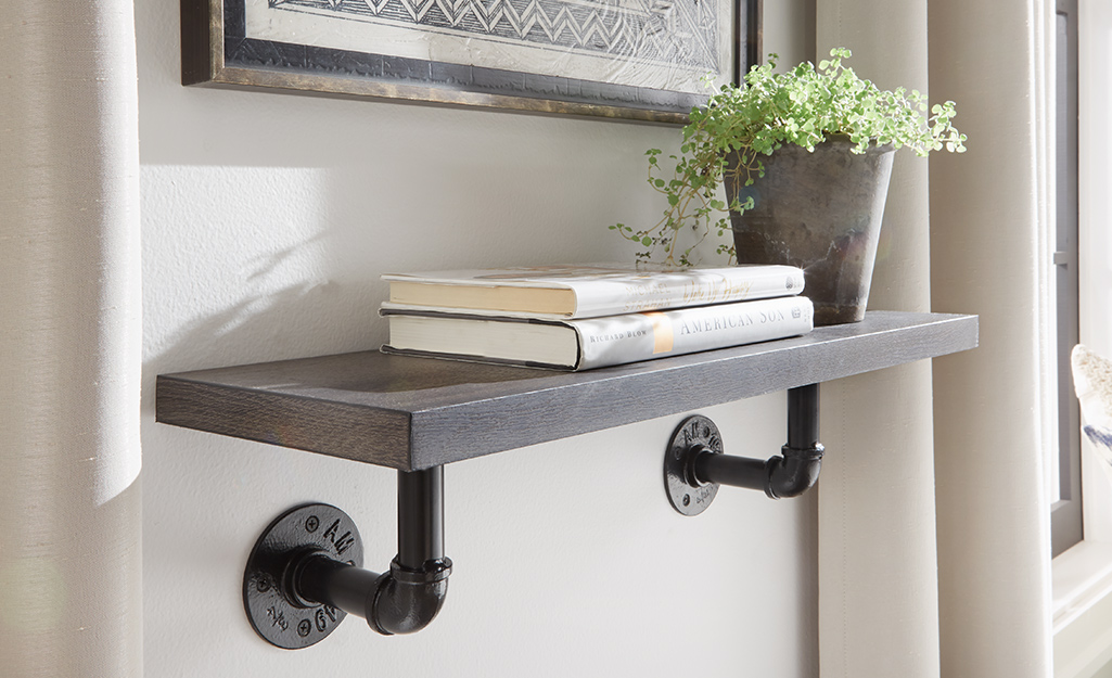 Một giá sách làm bằng gỗ và ống kim loại treo trên tường.