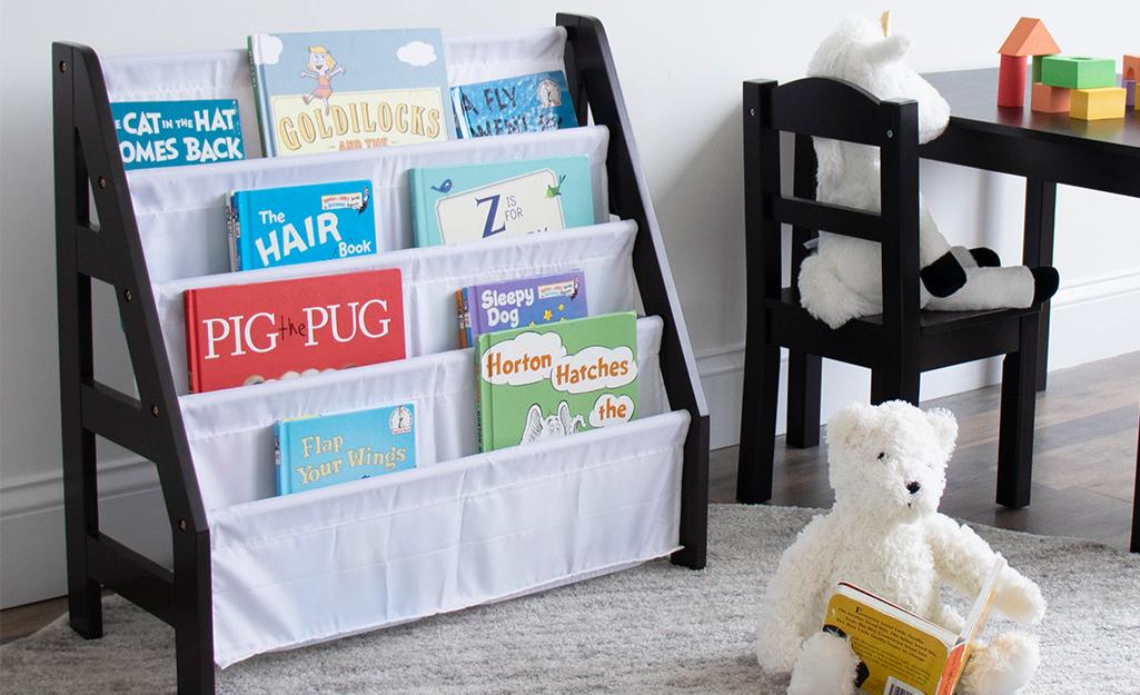 Một tủ sách màu đen được trang trí bằng rèm trắng trong phòng chơi của trẻ nhỏ.