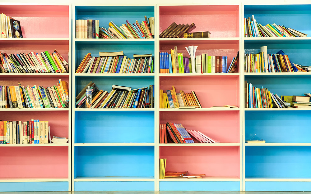 Bookcases painted in alternating colors of pink and blue.