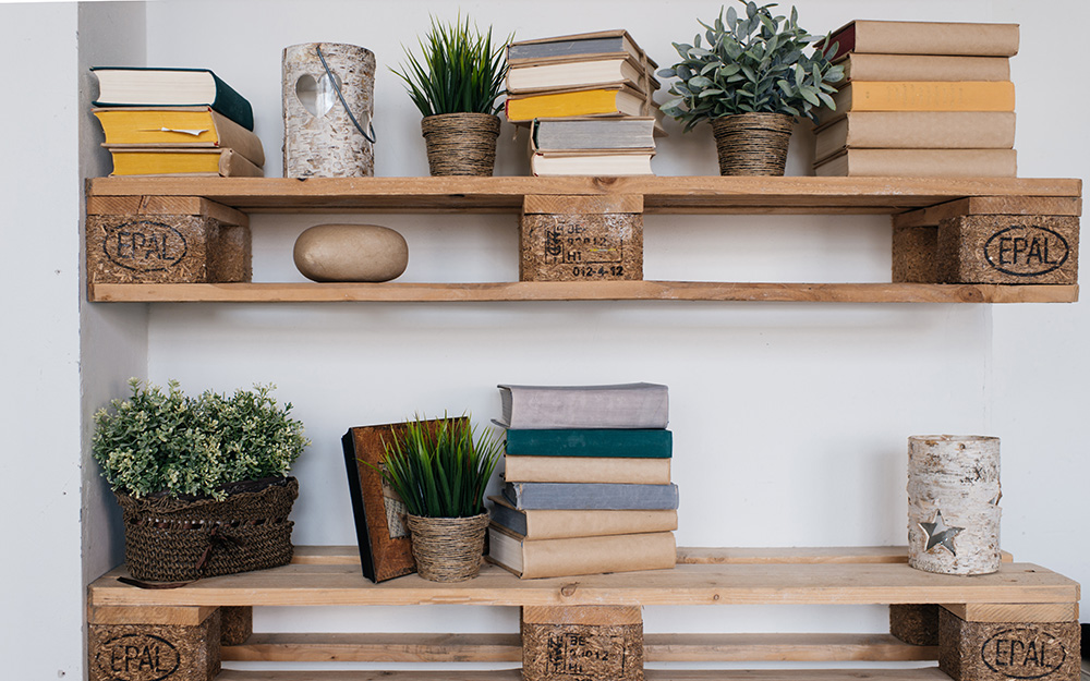 Bookshelves made from wooden pallets hang on a wall.
