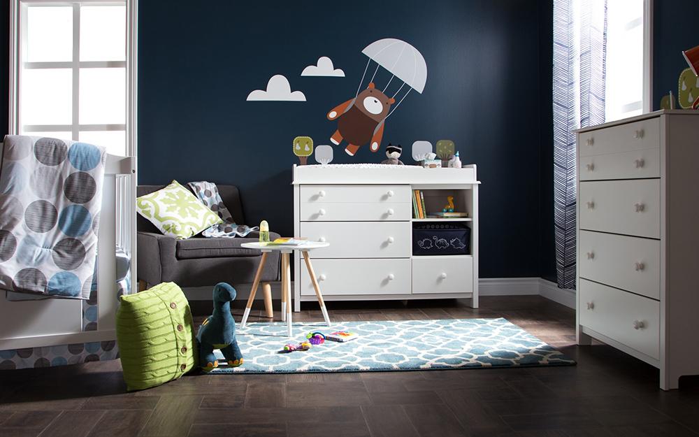 Nhà trẻ của một cậu bé với những bức tường tối màu, đồ nội thất màu trắng và decal hình một con gấu đang nhảy dù.