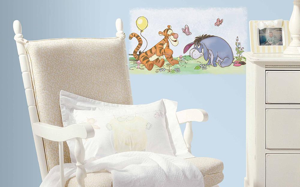 Một nhà trẻ với những bức tường xanh lam, một chiếc ghế bập bênh màu trắng và các nhân vật Winnie the Pooh trên tường.