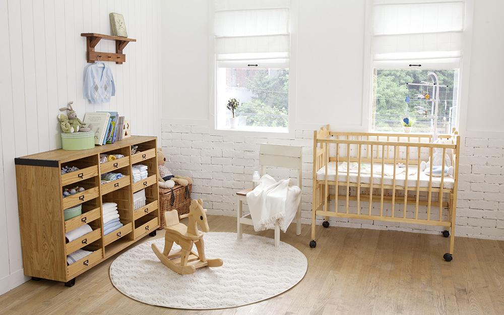 Phòng trẻ của một cậu bé với màu sơn trung tính và sàn gỗ sáng màu.