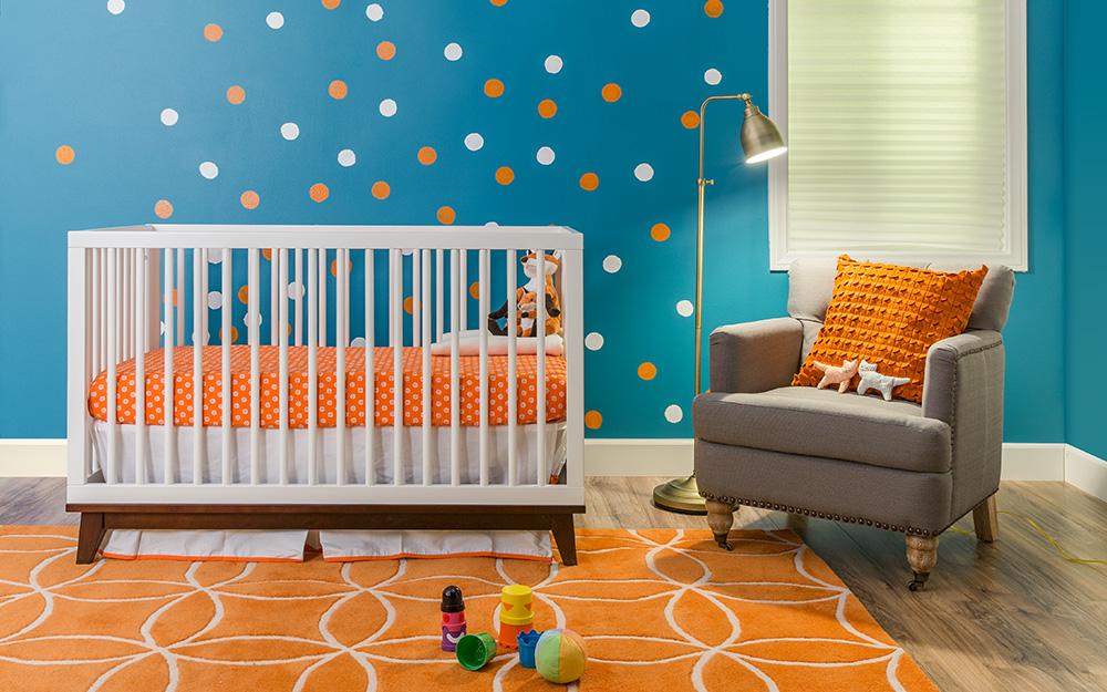 Một nhà trẻ với bức tường màu xanh lam và chấm bi trắng và cam cùng các phụ kiện có màu sắc phù hợp.