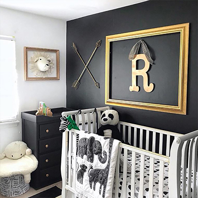 A boy's nursery with an accent wall painted in a dark color and his initial framed and hung over the crib.