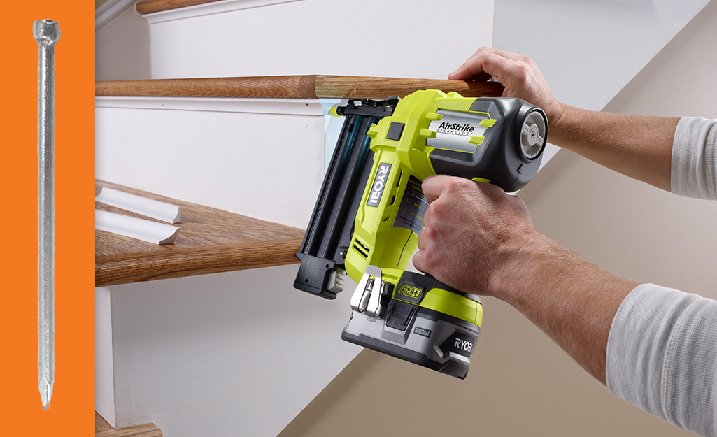A person using a nailer to fasten trim to stair risers.