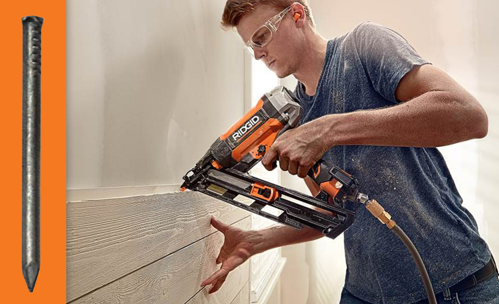 A person using a nailer to fasten trim to a wall.