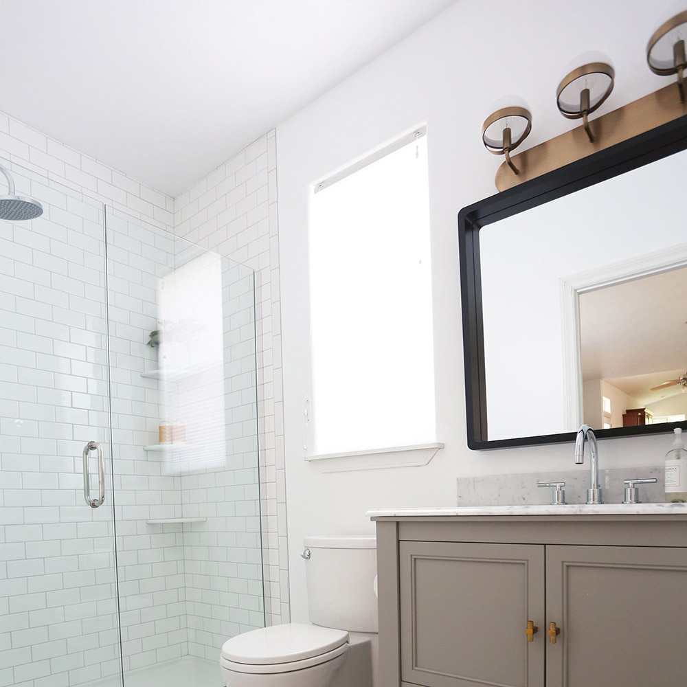 A bathroom with a gray vanity and tiled shower.