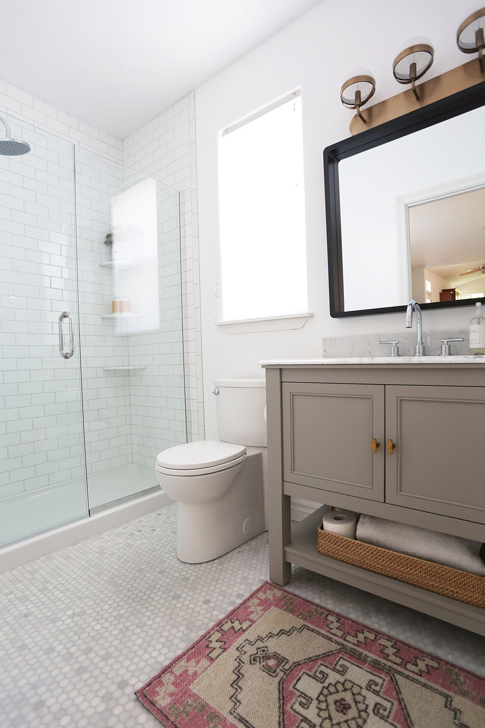 An updated bathroom with a tiled shower, tiled floor, and new gray vanity.