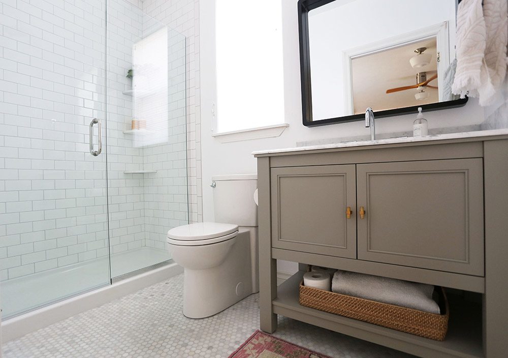 An updated bathroom with a new vanity, toilet, and tiled shower.