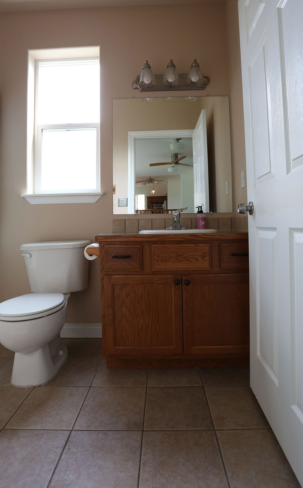 An outdated bathroom with an old wooden vanity and beige tile floors.