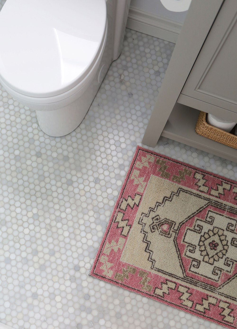 A pink patterned rug sitting on a white hexagon tile floor.