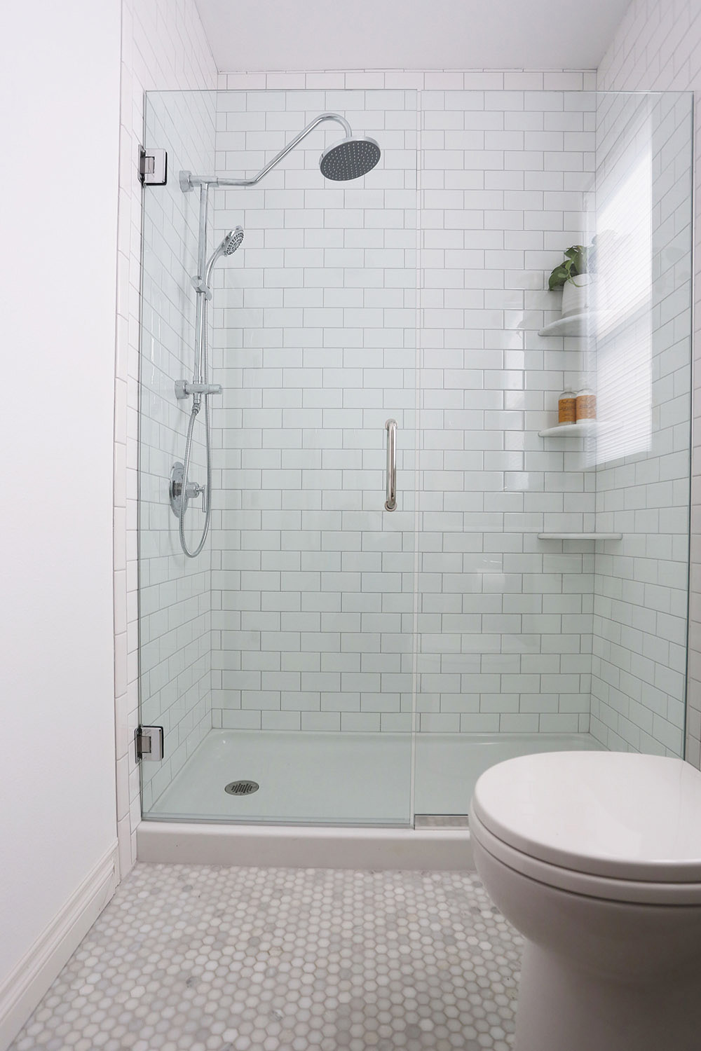 A walk-in shower with white subway tile walls and a glass door.