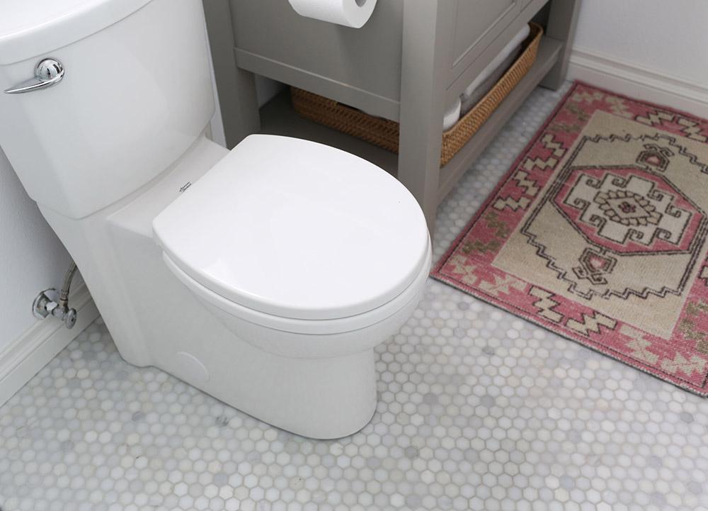 A new streamlined toilet on a white hexagon tile floor.