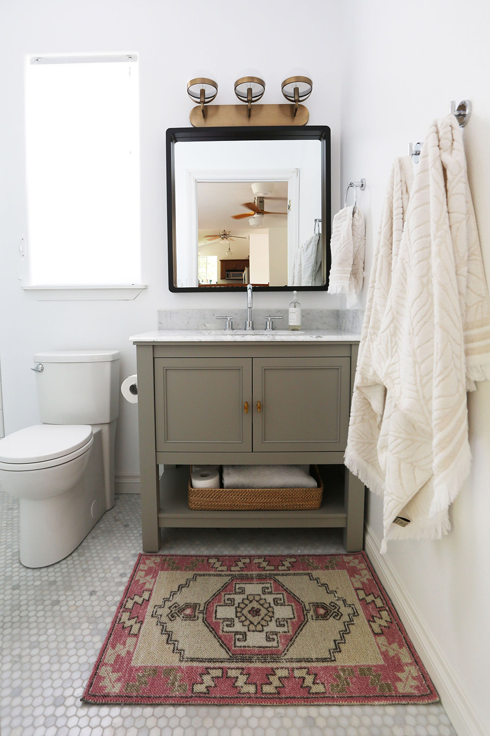 A gray vanity with a white marble top.