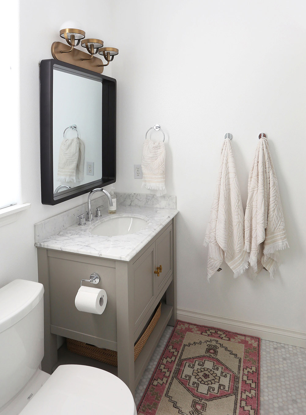 A modern square black mirror with rounded edges hangs over a bathroom vanity.