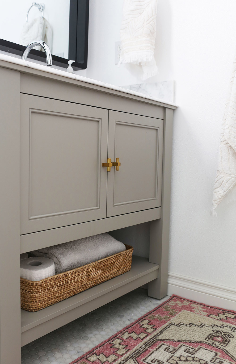 A gray vanity with brass knobs.