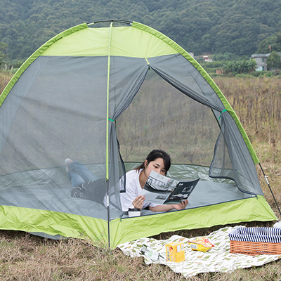 A person reads a magazine while reclining in a tent.