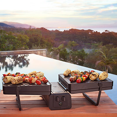 Food cooks on tabletop grills on a patio overlooking a mountain view.