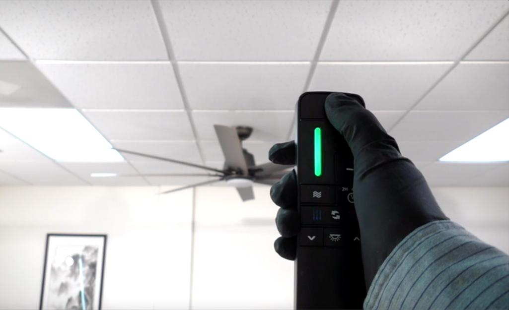 Một người sử dụng điều khiển từ xa của quạt trần trong văn phòng.
