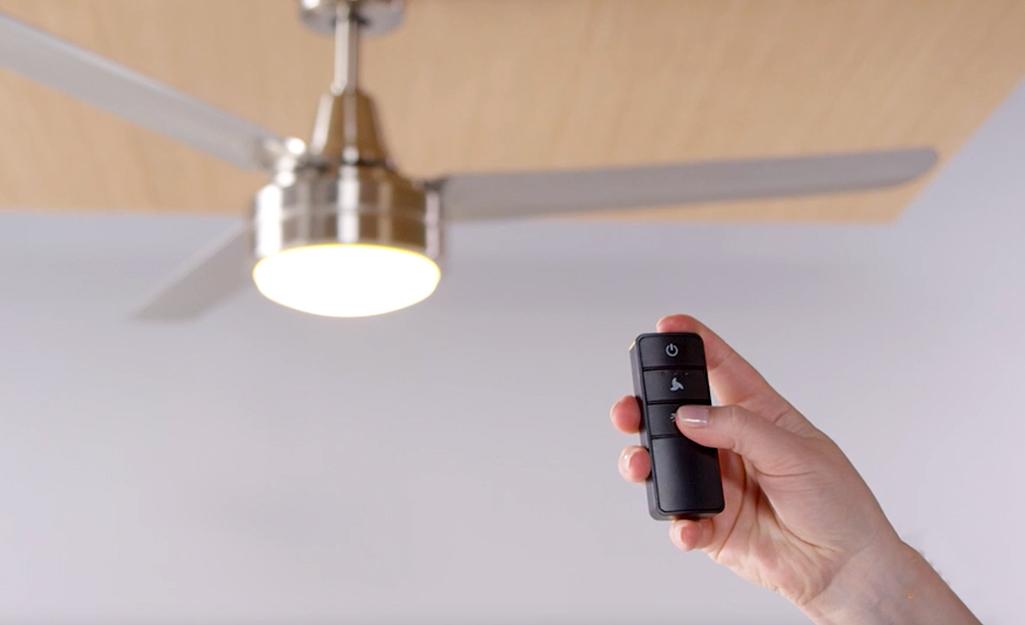 Một người sử dụng điều khiển từ xa trên quạt trần.