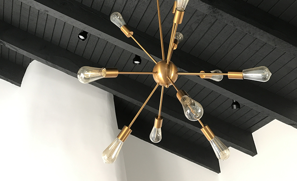 A gold light fixture on a black ceiling.