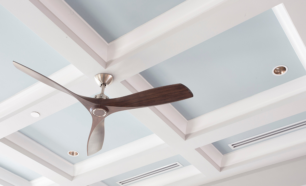 A coffered ceiling painted blue with a ceiling fan.