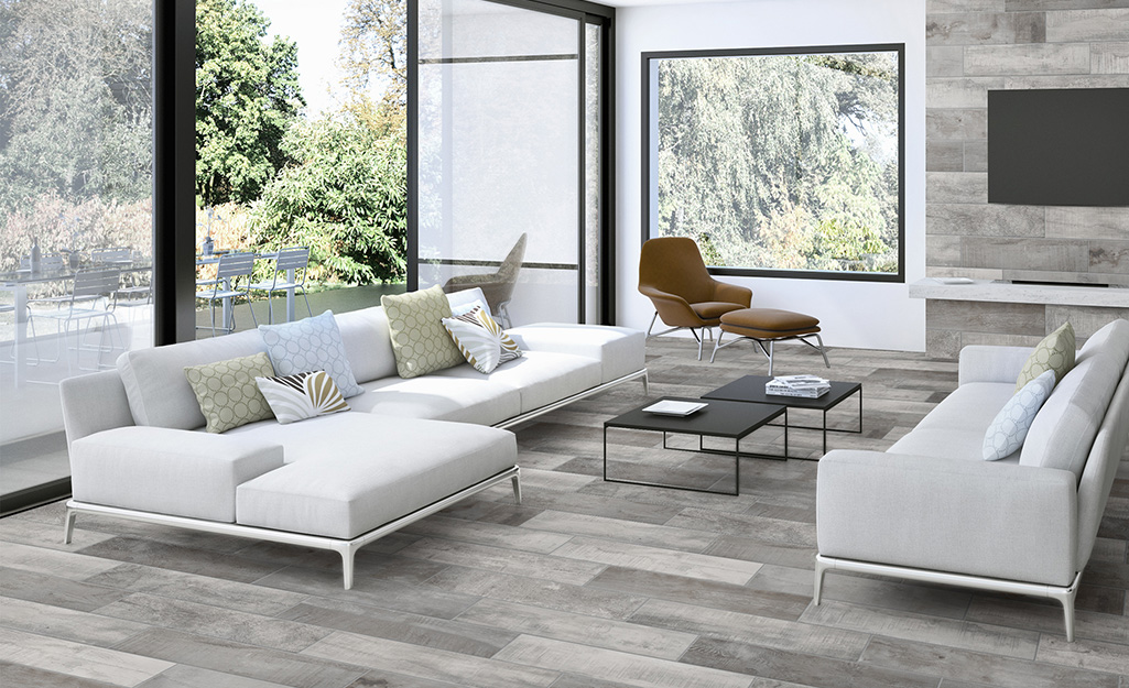 A sunroom with furniture standing on porcelain tile.