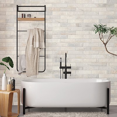 A bathroom with a porcelain tile floor and ceramic tile on the wall.