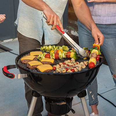 A person cooks skewers and burgers on a charcoal kettle grill.