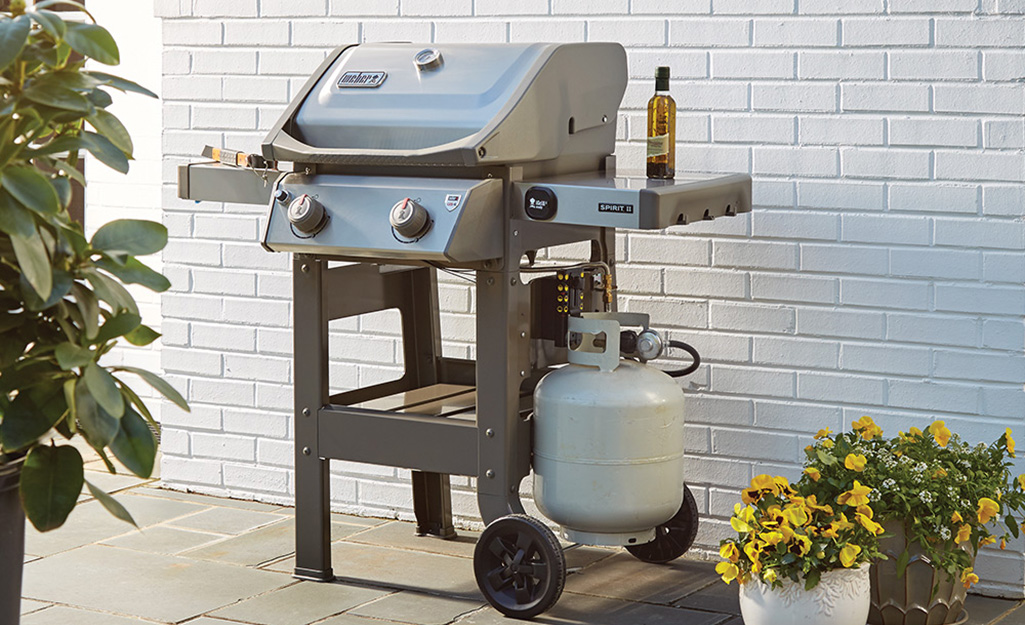 A gas grill with a propane tank on a patio.