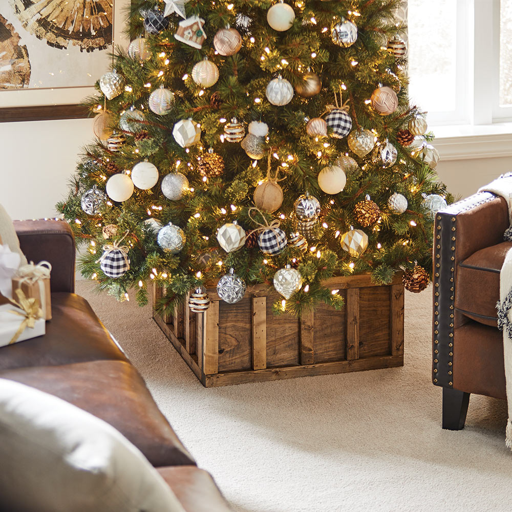 A completed Christmas tree stand box in a living room, holding a decorated Christmas tree.