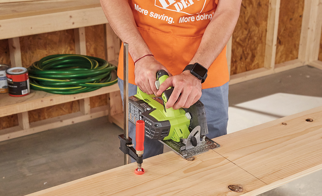 Someone using a circular saw to cut a board for the Christmas tree stand box.