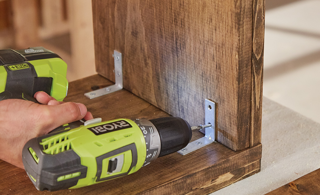 Someone using a drill to install corner braces for a Christmas tree stand box.