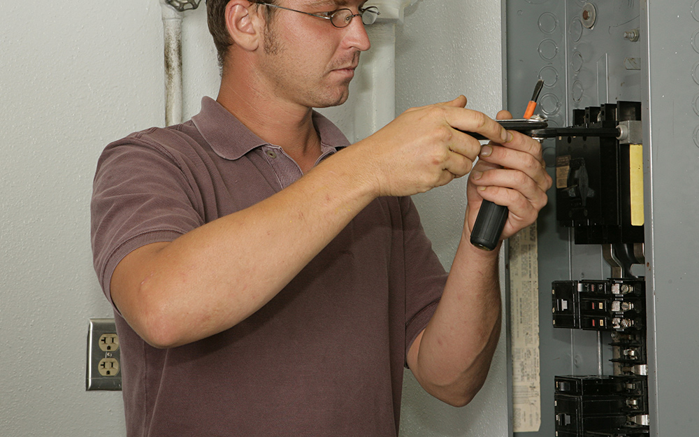 A person installing a circuit breaker into an electrical panel.