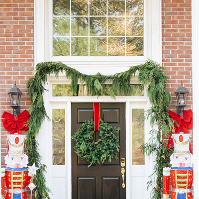 A front door decorated with a wreath, garland, and two large nutcrackers.